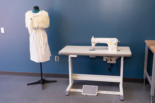 industrial sewing machine with dress and fake fur cape