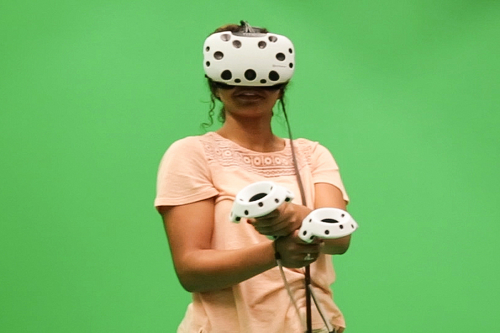 student with VR helmet in front of green screen