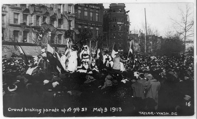 Woman's suffrage procession in Washington, D.C. being stopped by a crowd.