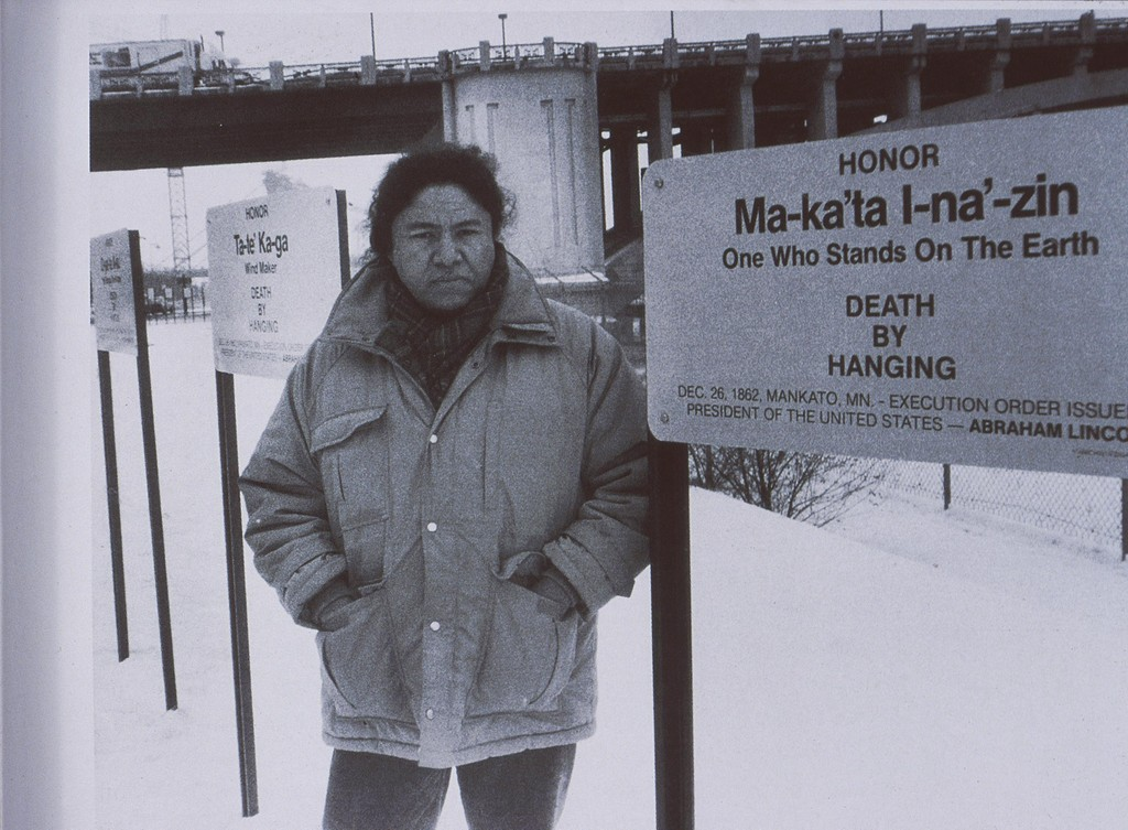 Photograph of Edgar Heap of Birds standing in an installation in Minnesota in 1990.