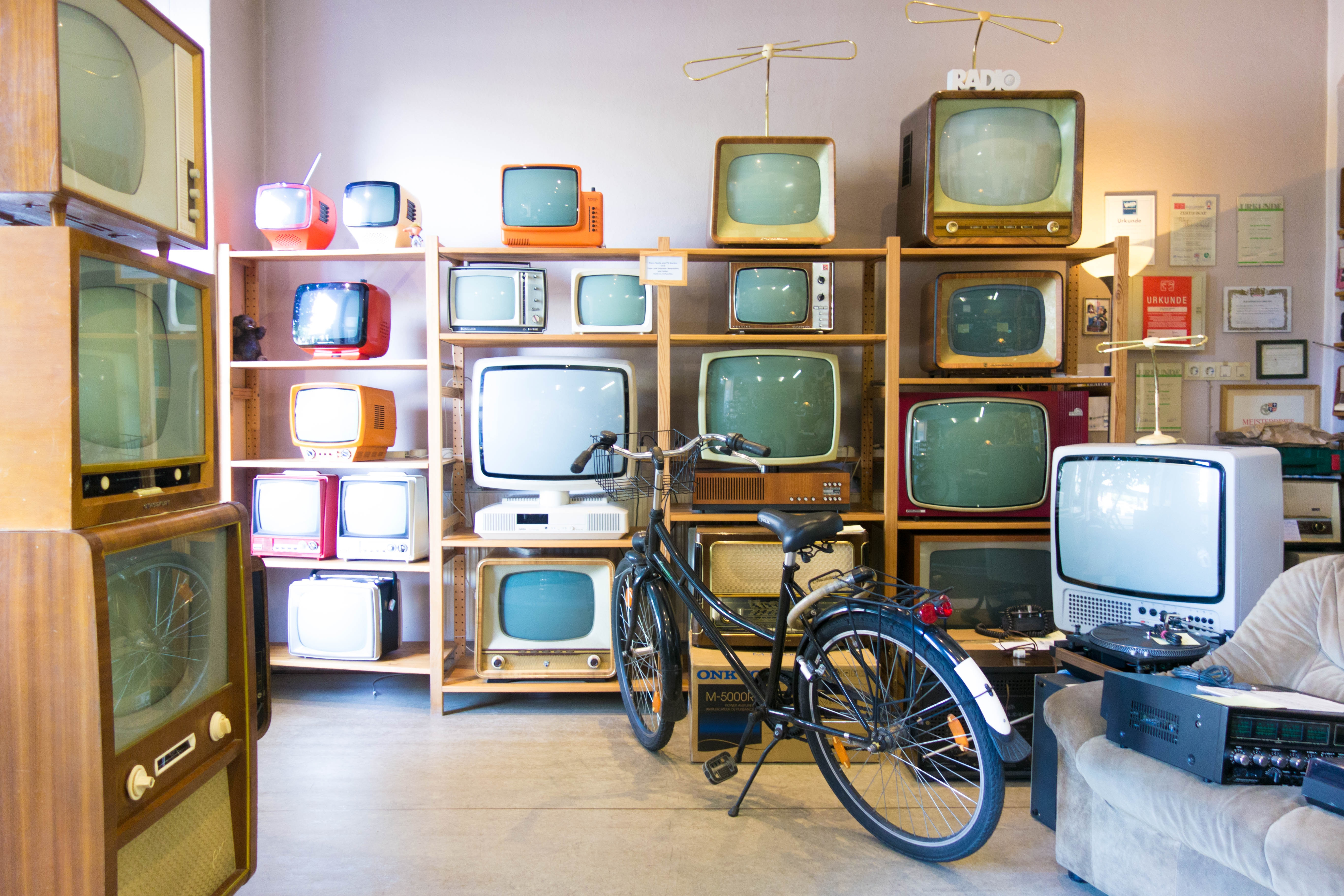 Picture of several vintage televisions on  shelf. A bike is propped up in front of them.