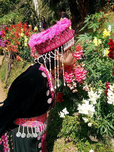 Hmong youth in brightly colored native garb smelling flowers in equally brightly colored garden