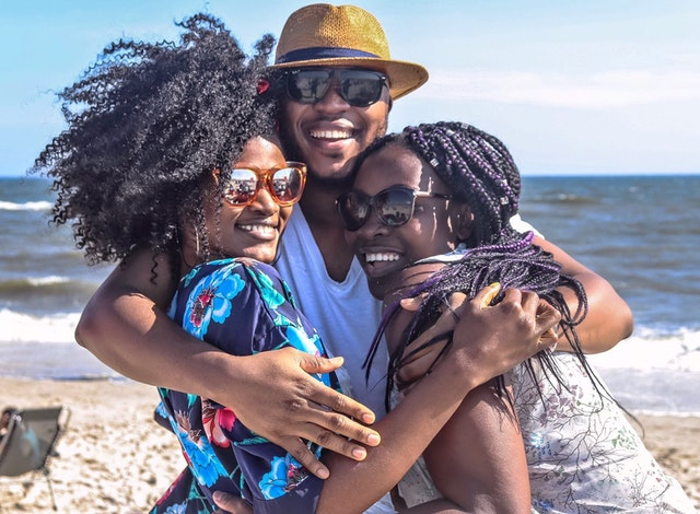Image of three young black people embracing at the beach