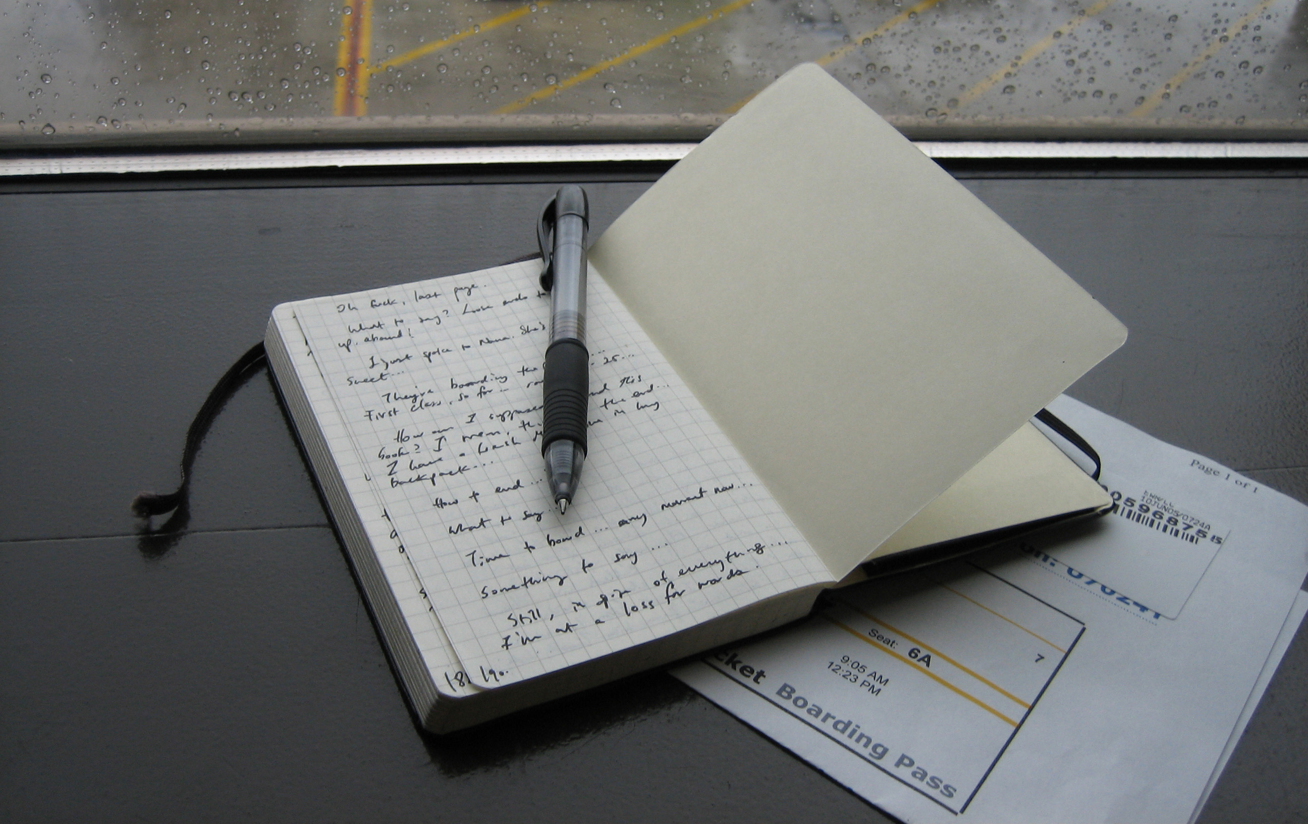Image of a notebook with a pen on a table near a rainy window