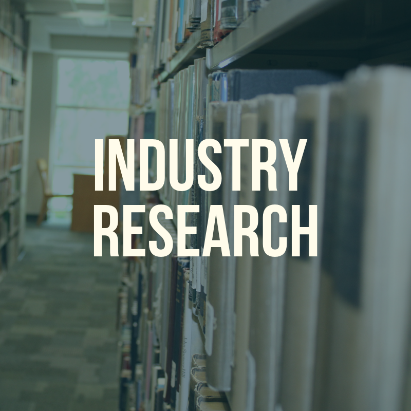 "Picture of the library shelves with the word ""Industry Research"" to label this guide."