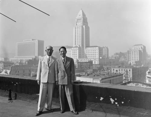 Two men on top of building with downtown Los Angel
