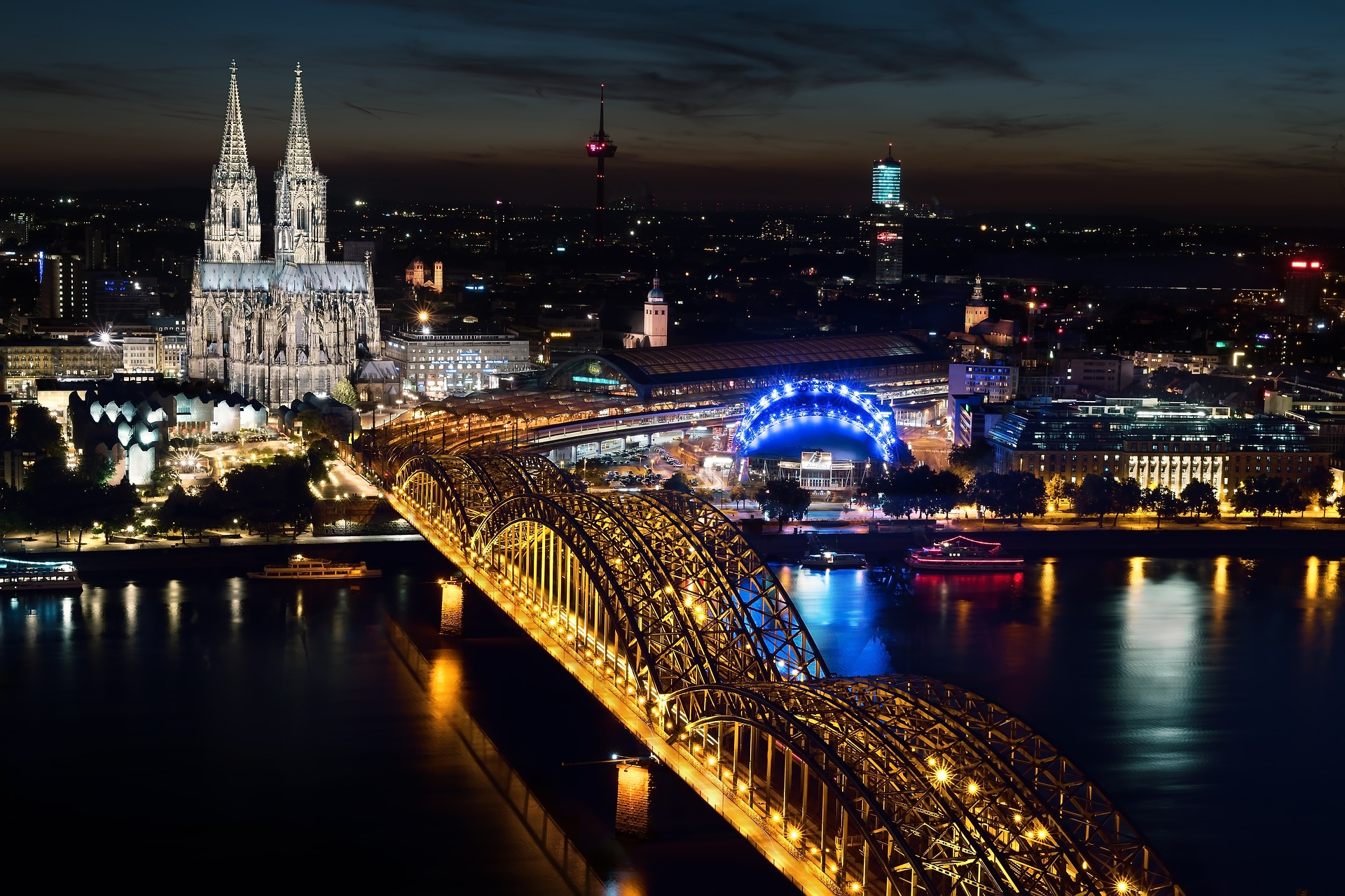 Picture of the Cologne, Germany skyline at night featuring the Cologne Cathedral and the Hohenzolleran Bridge over the Rhine River.