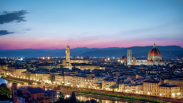 Picture of the skyline of Florence at dusk featuring the Duomo, Palazzo Vecchio, and the Arno River in the foreground.