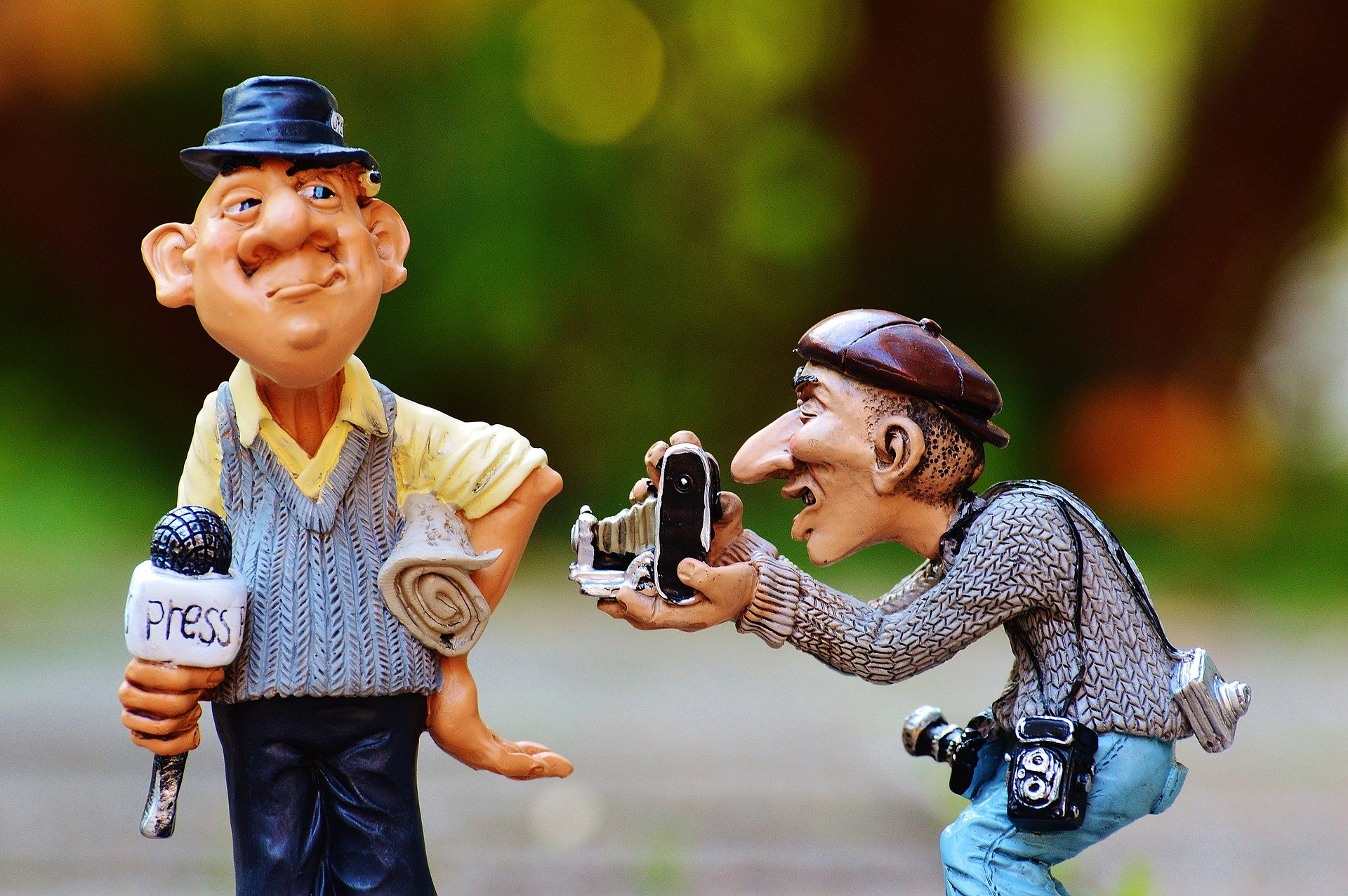 Photograph of a cartoon-like figurines of a journalist, holding a microphone and a rolled up newspaper, and a photographer, holding a camera and photographing the journalist.