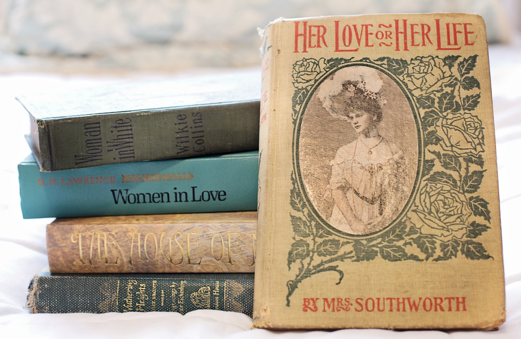 "A stack of books, including ""Her Love or Her Life"" by Emma D.E.N. Southworth, ""The Woman in White"" by Wilkie Collins, ""The House of Mirth"" by Edith Wharton, ""Women in Love"" by D.H. Lawrence, and ""Wuthering Heights"" by Emily Bronte."