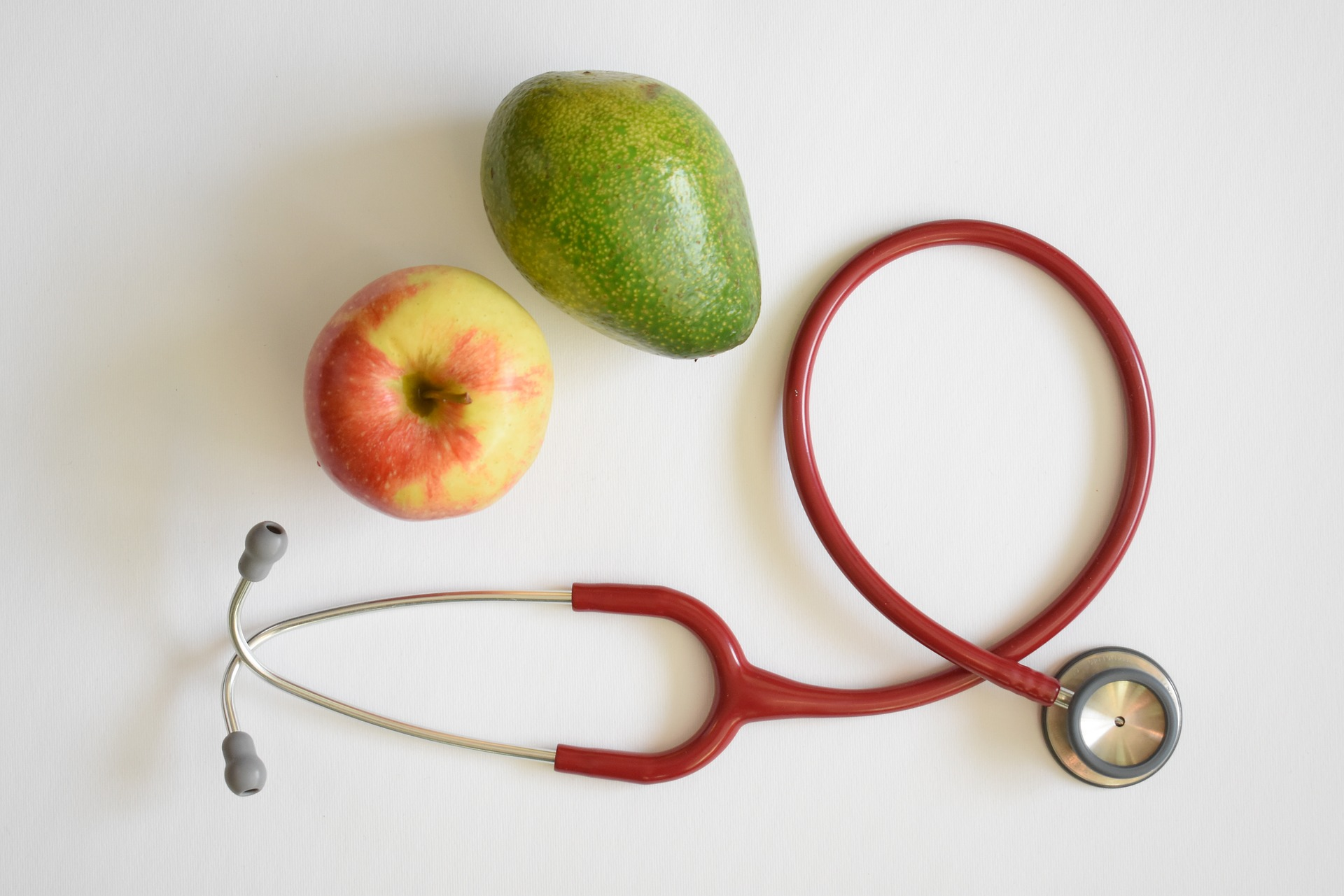Image of stethoscope, apple, and avocado on white background.