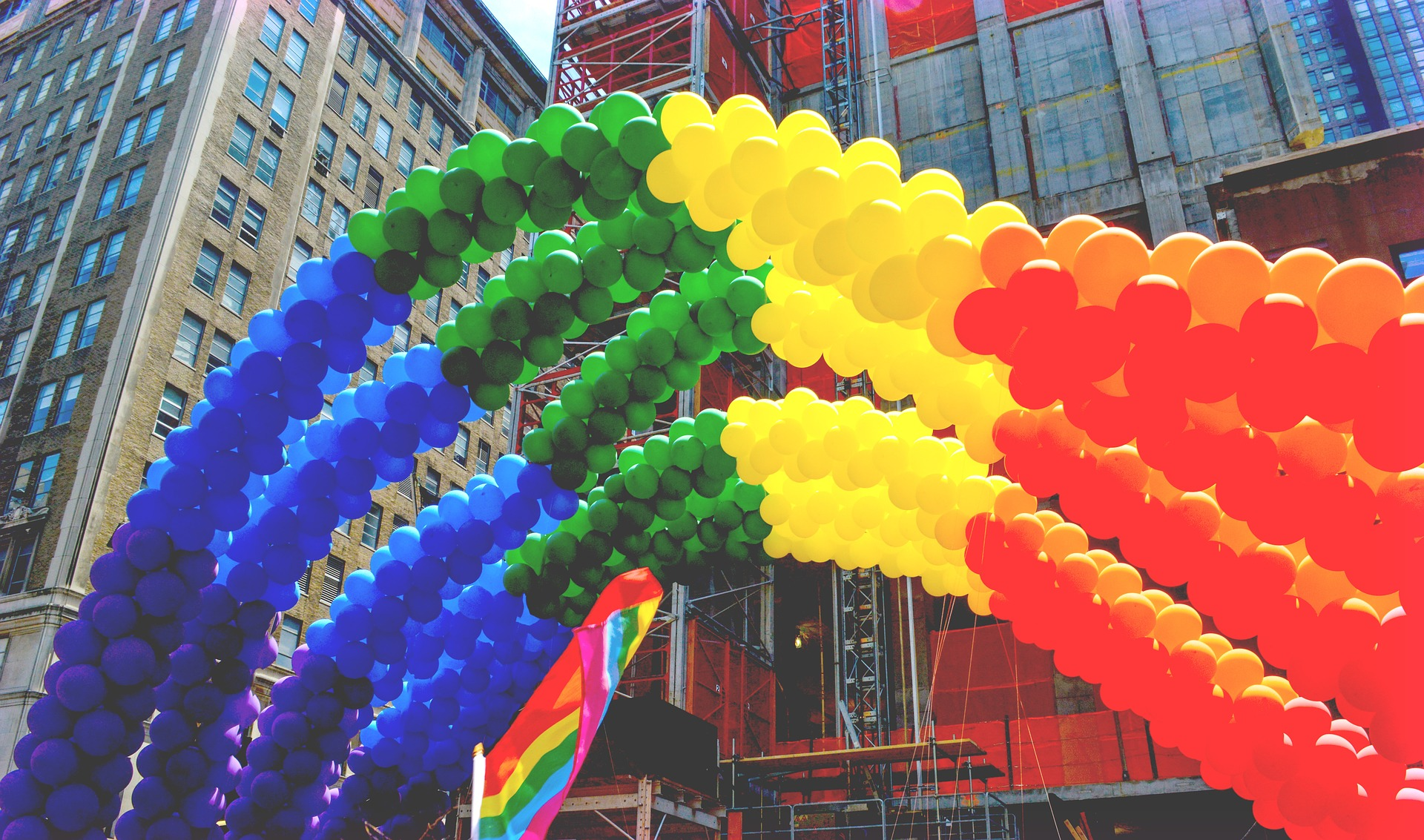 Image of rainbow balloon arch over a pride flag. Skyscrapers are in the background.