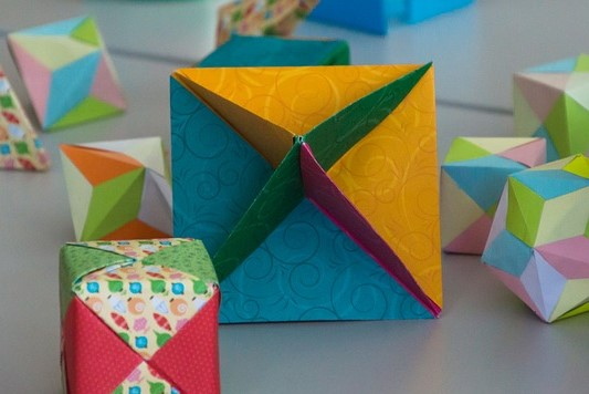 Image of geometric shapes made of colorful origami paper.