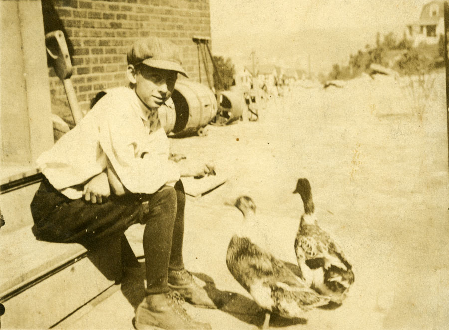 Young Harlan Hubbard sitting on a step outside a building, with two geese in front of him