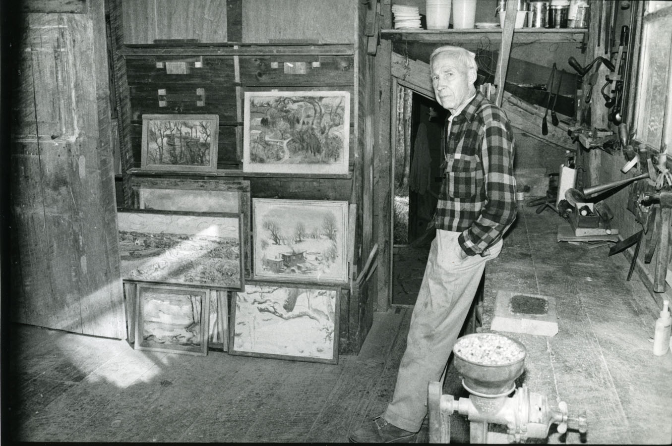 Harlan Hubbard in his studio, with paintings; photo by Guy Mendes
