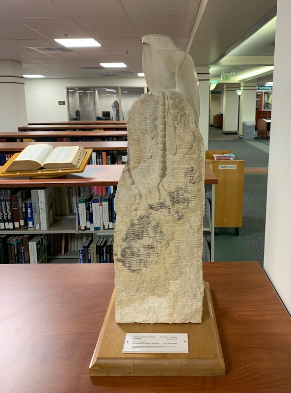 Photograph of hawk sculpture sitting on top reference collection shelves