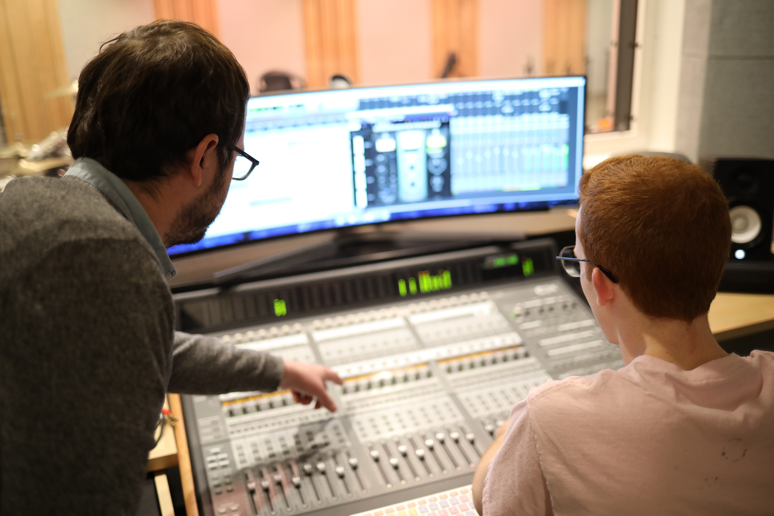A staff member and student work together on a recording studio panel.