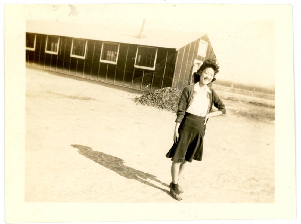 Aiko Herzig Yoshinaga at the Jerome or Rowher incarceration camp. Incarceration camp barracks are pictured behind her.