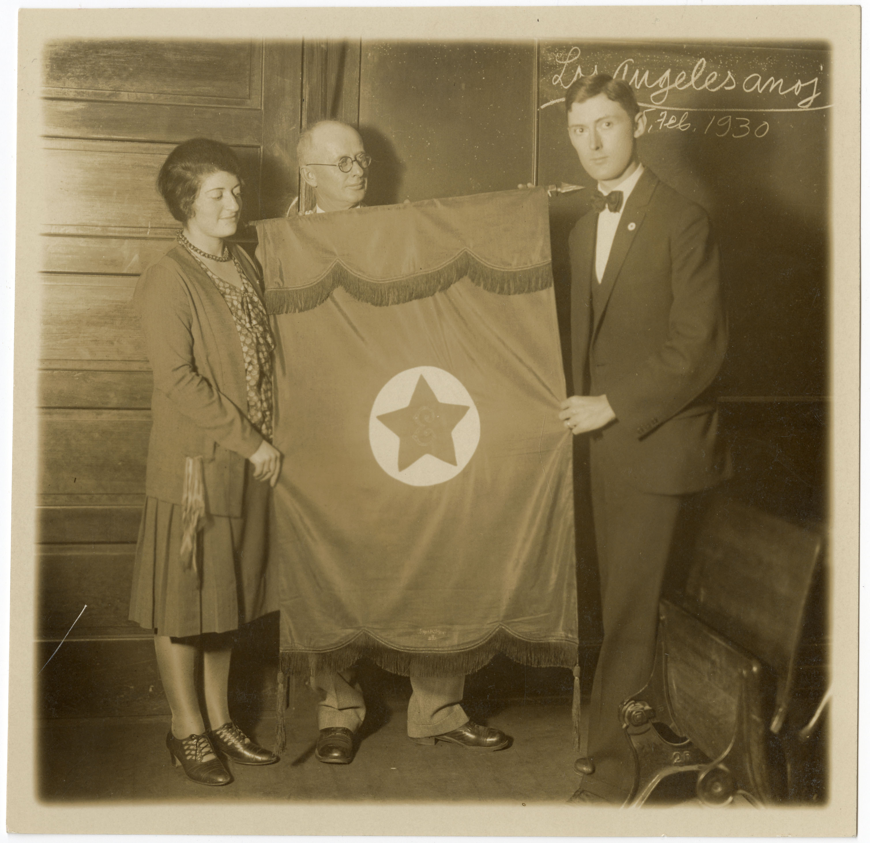 Joseph Scherer with two others holding an Esperanto flag