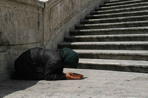 Image of a person begging at the foot of a staircase