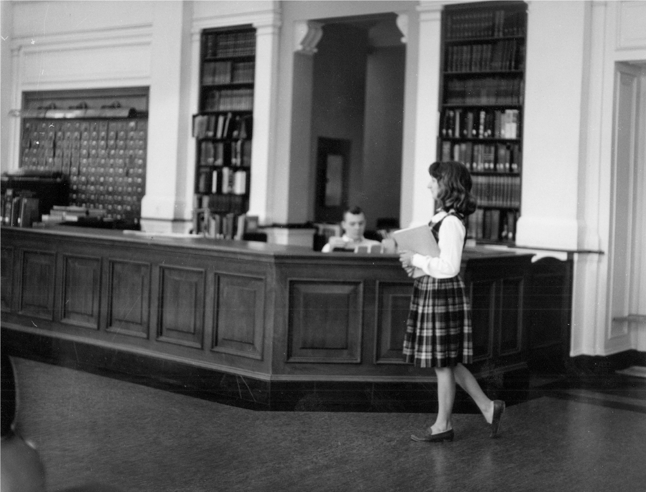 Woman walking in front of Morrow Library circulation desk.