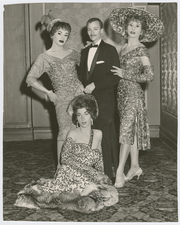 Black and white photo of Storme DeLarverie in drag, wearing a tuxedo. Two women in drag are on his left and right, and another woman in drag is seated at his feet.