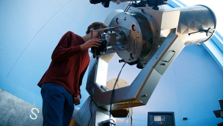 Photograph of a student looking into a very large telescope.