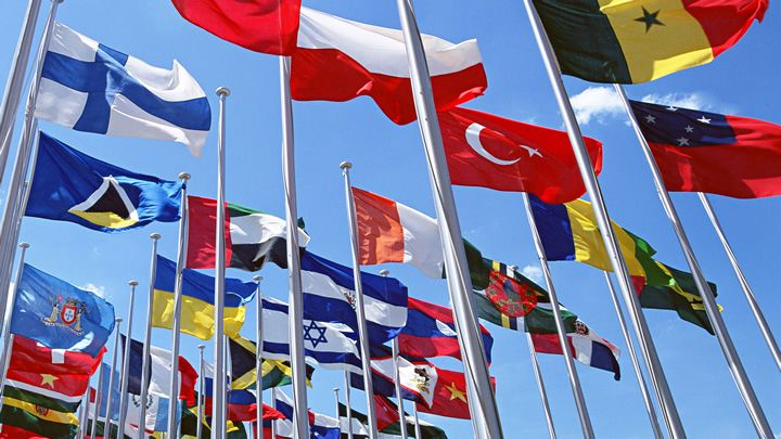 Photograph of a multitude of flags from different countries waving in the wind.