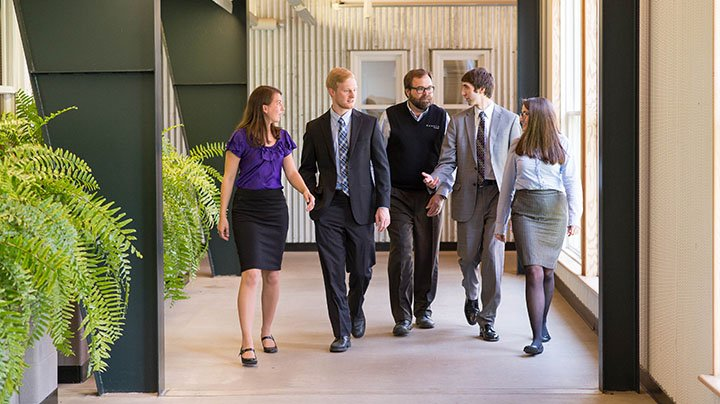 Photograph of five people in business attire walking down a corridor.