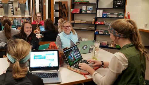 Photograph of a group of smiling students sitting around a table with open laptops.
