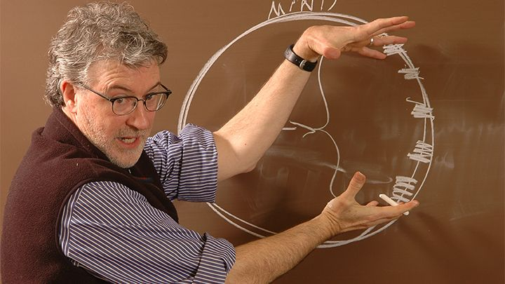 Photograph of a professor gesticulating in front of a chalk board with a circle diagram drawn on it.