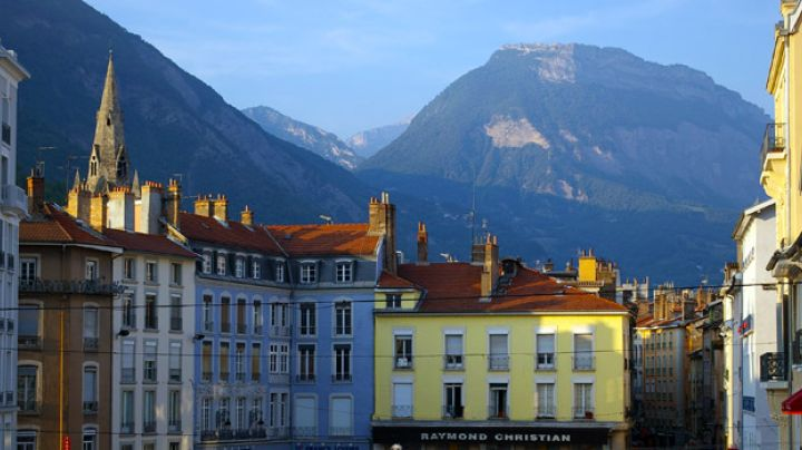 Photograph of French buildings with tall mountains in the background.