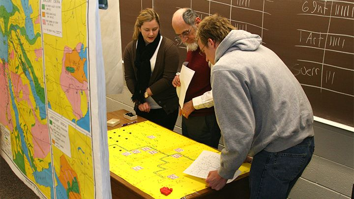 Photograph of three people standing in front of a map and studying a timeline.