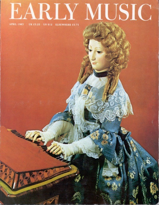 Journal Cover - Title in white lettering over a photograph of a doll sitting at a play organ against an auburn background.