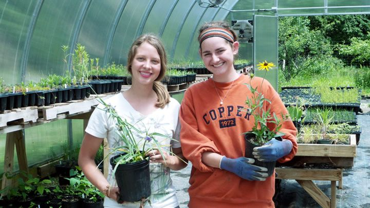 Photograph of two girls standing in a greenhouse and holding plotted plants.