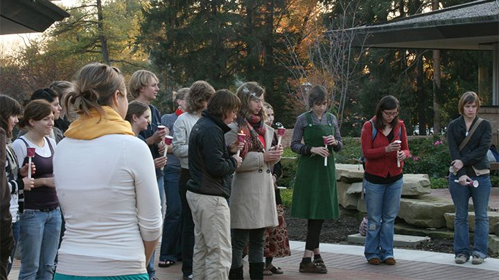 Photograph of group of students standing outside of the chapel in a circle, holding candles and praying.