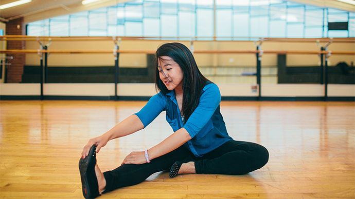 Photograph of a girl sitting in a dance studio, stretching her legs.