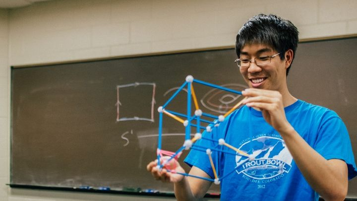 Photograph of a student holding an object made up of blue and orange sticks connected by white balls.