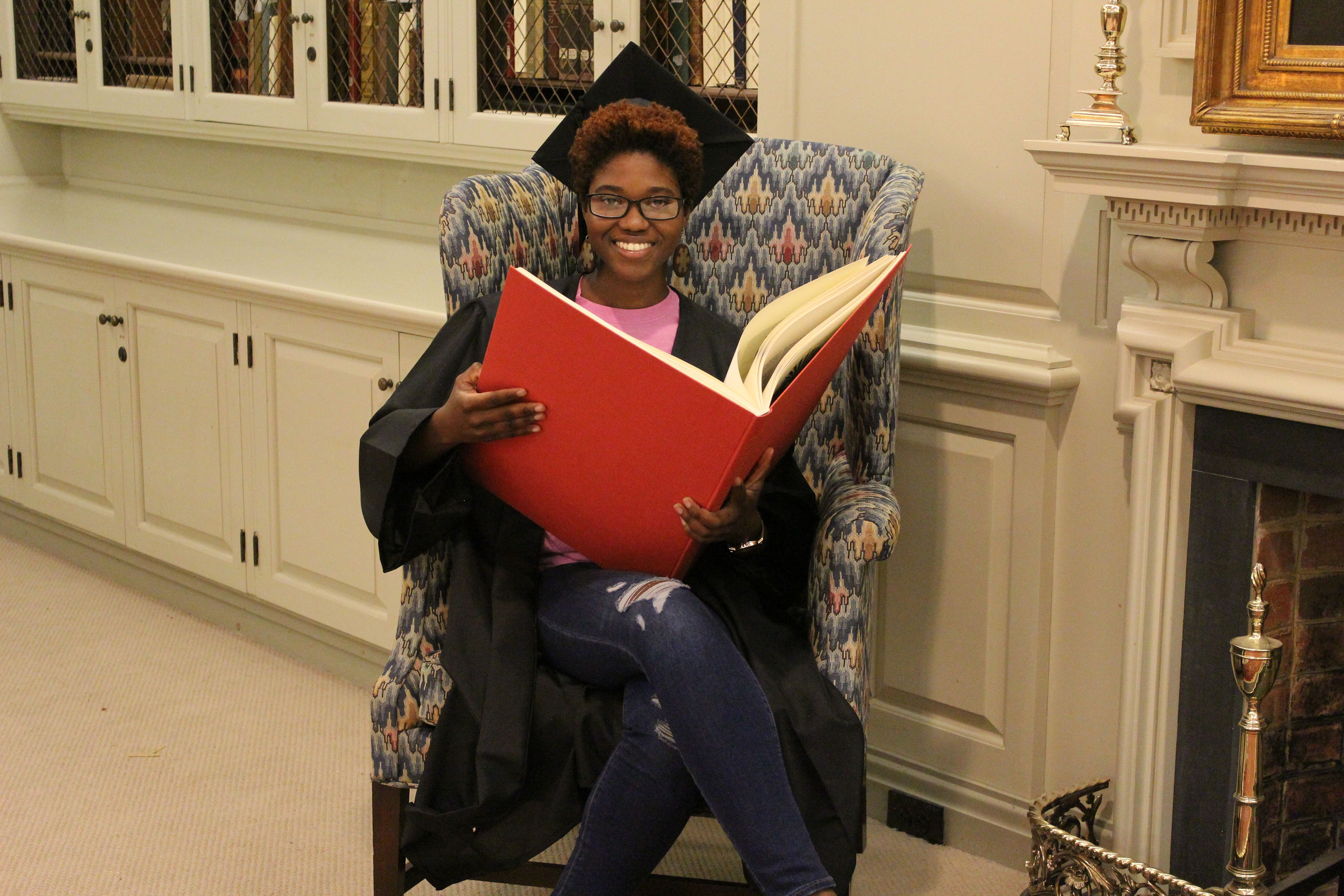 Female Student Holding Huge Book in Rare Book Room Couch