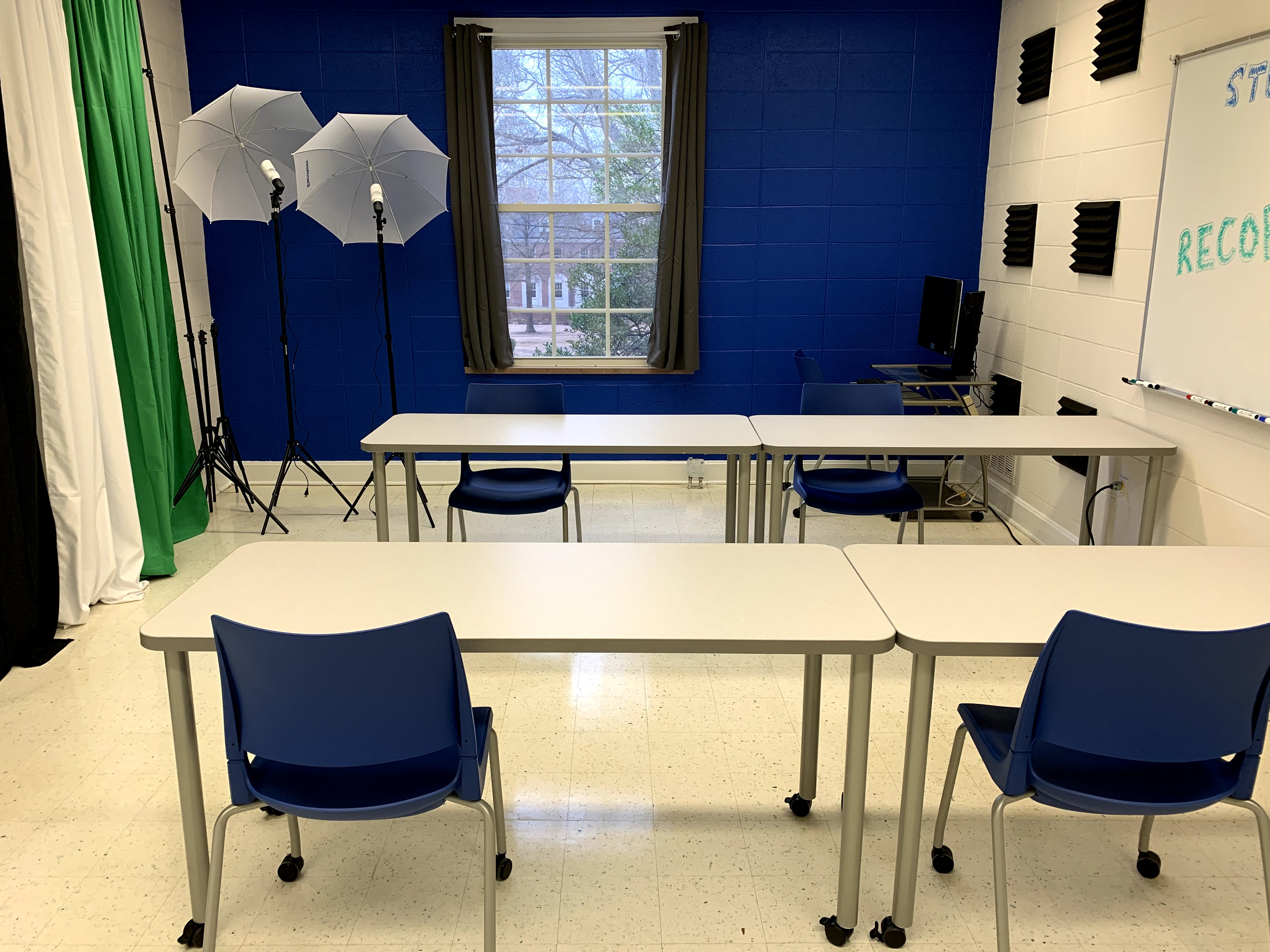 room with black, white, and green backdrops, umbrella lights, tables, chairs, and whiteboard