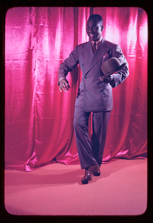 Color Photograph of tap dancer Bill Robinson in a grey suit and hat with a pink curtain as the background.
