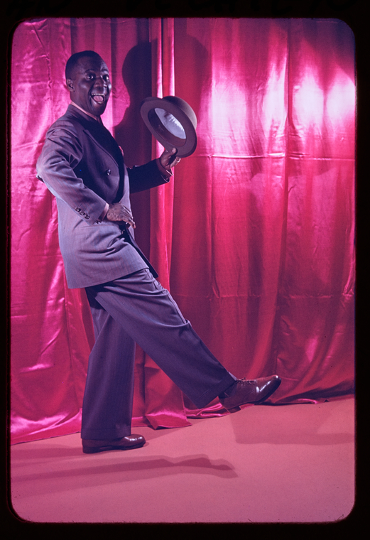Color Photograph of tap dancer Bill Robinson in  a suit and hat with a [pink curtain as the background.