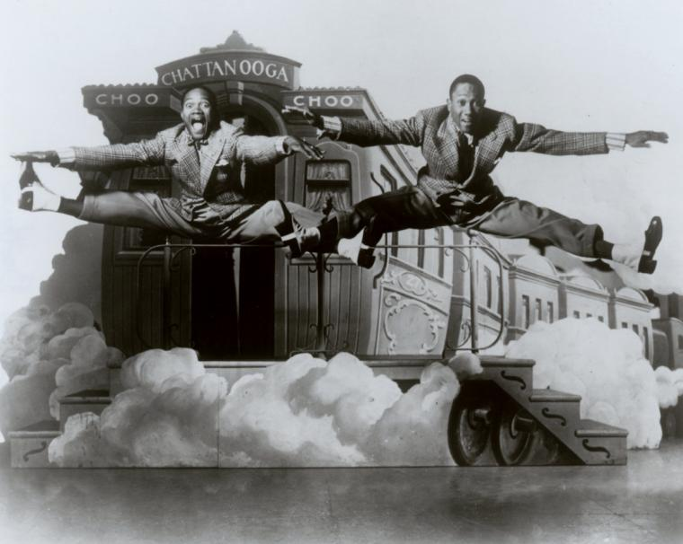 "The Nicholas Brothers in side split leaps in front of a stage set featuring a railroad caboose labeled ""Chatanooga Choo Choo"". Jerome Robbins Dance Division Photography Files *MGZEA."