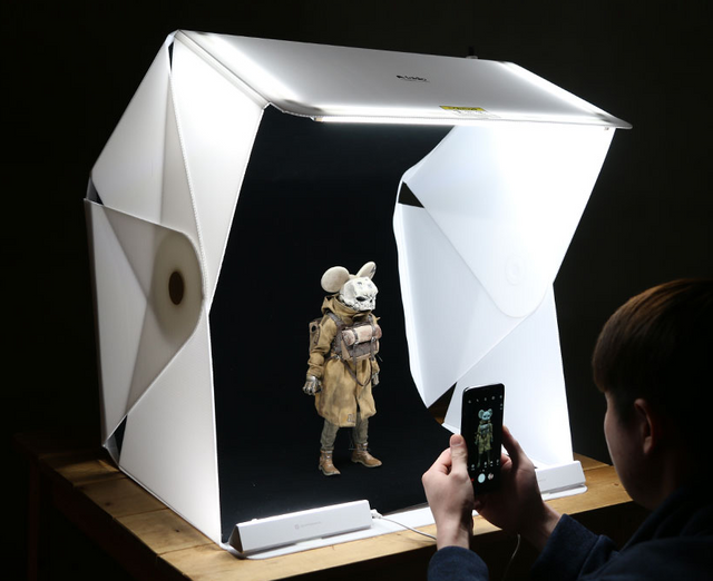 photo box with figurine getting picture taken