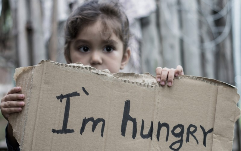 child with I'm hungry written on cardboard sign