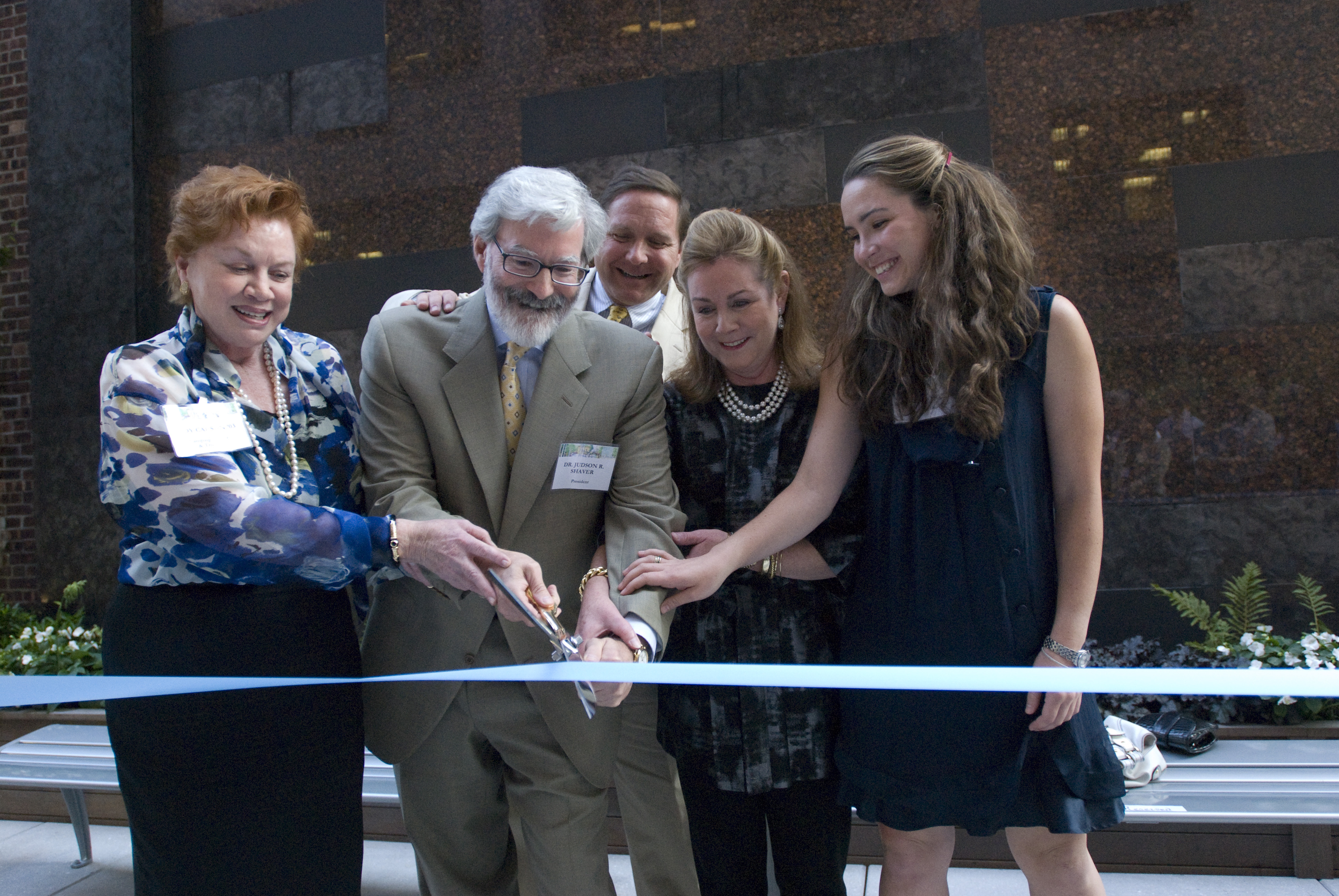 Outdoor ribbon-cutting ceremony with five people.