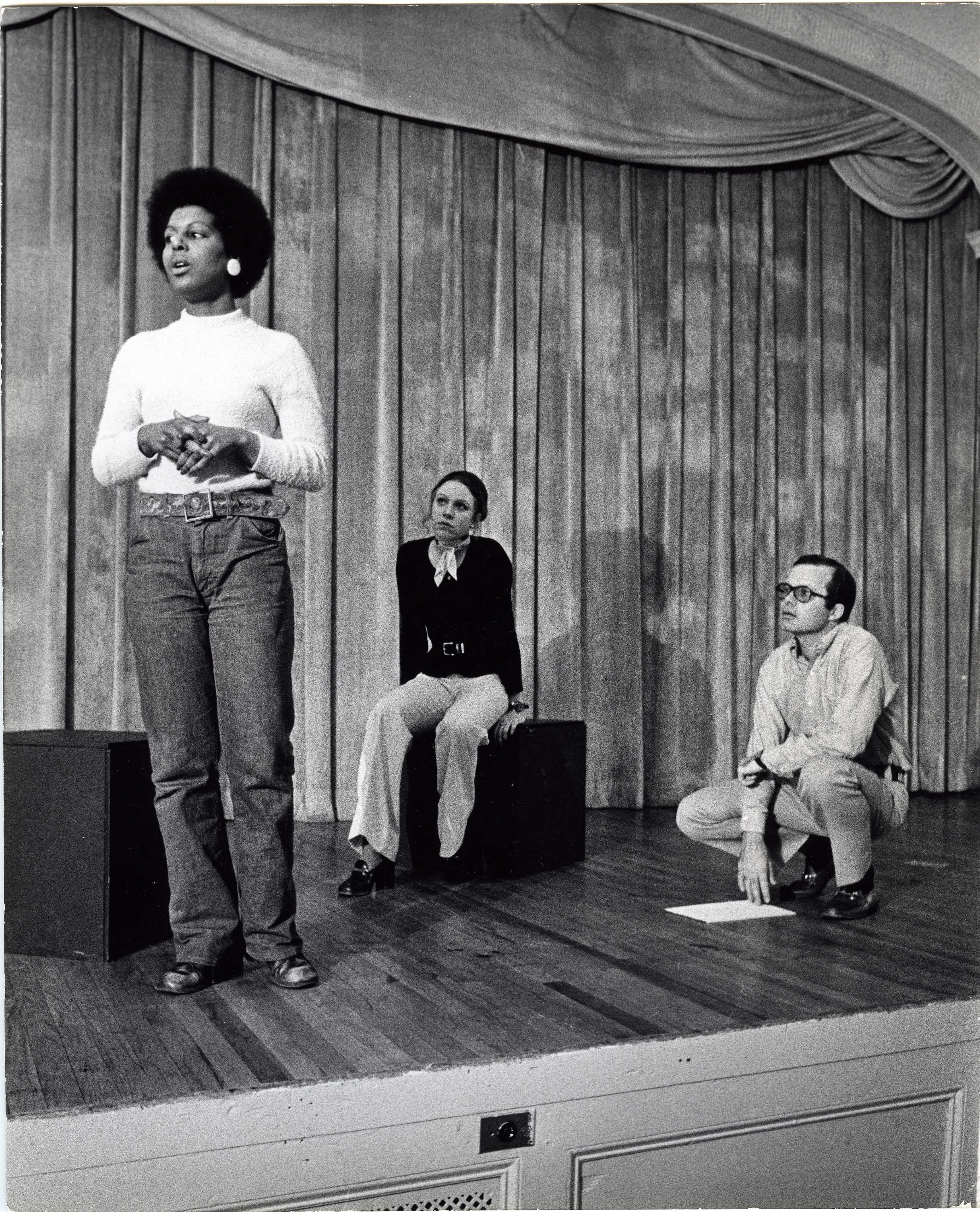 Bill Bordeau crouching on stage in Great Hall directing two female actors, 1972