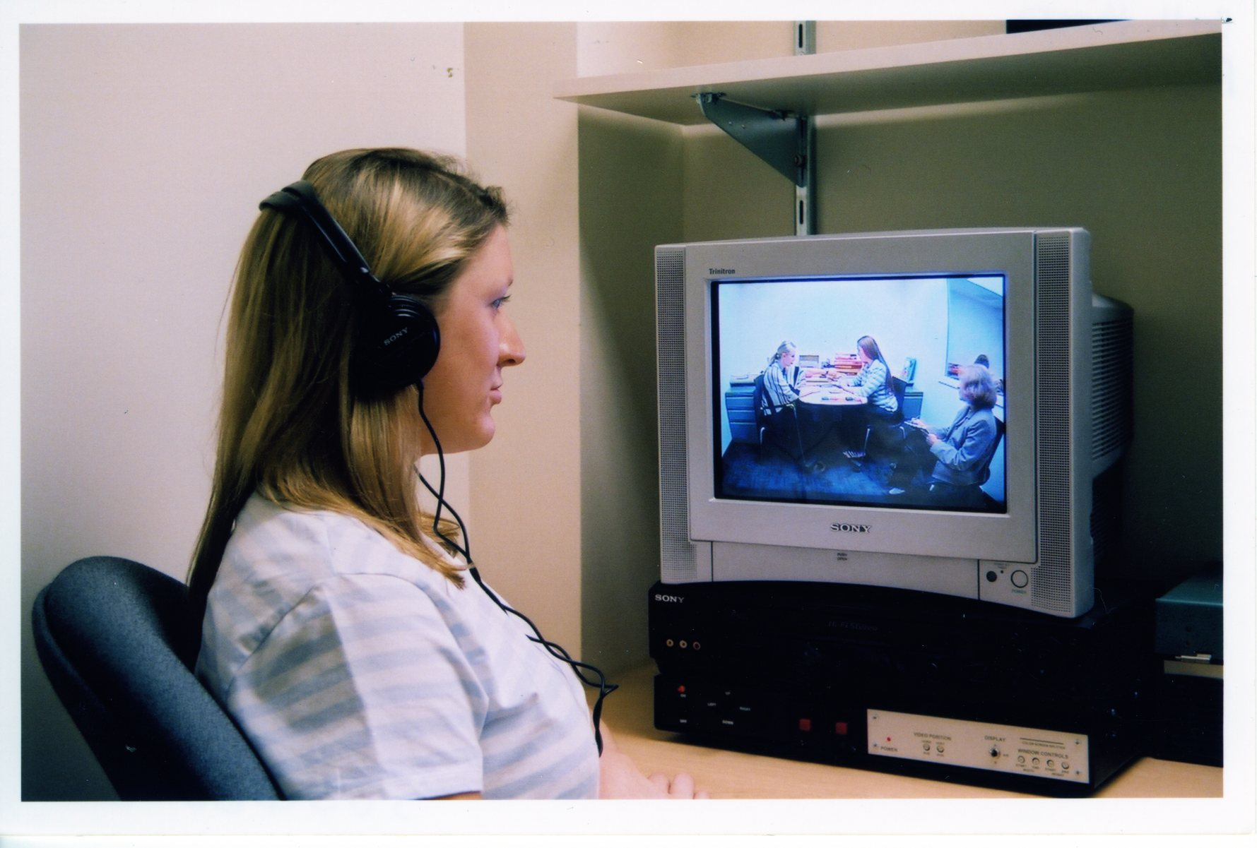 Student observing speech-pathology treatment via closed-circuit television and headphones.