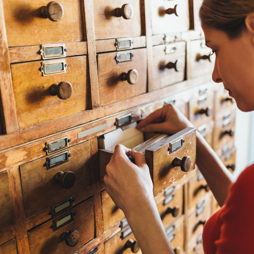 Woman opening a card catalog drawer