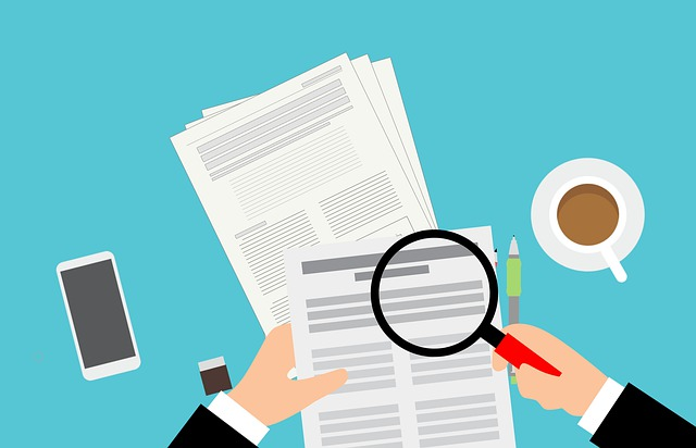 Animated image of stacks of papers with a magnifying glass hovering over it, as though a person is looking down at their desk; a smartphone and coffee cup are on either side of the image